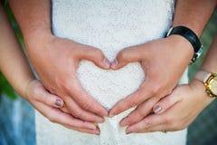 Les femmes enceintes enroulent ses bras autour du ventre Photographie stock libre de droits