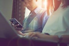 Les femmes et les hommes sont des amis Les concepts d'informatique de téléphone et de jeu font nos vies dépasser Photo libre de droits