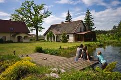 Les femmes et la fille s'asseyant par un village logent la piscine image libre de droits
