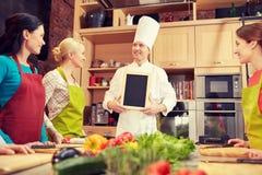 Les femmes et le chef heureux font cuire avec le menu dans la cuisine Images stock