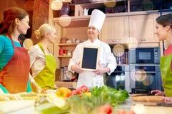 Les femmes et le chef heureux font cuire avec le menu dans la cuisine Photo libre de droits