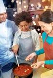 Les femmes et le chef heureux font cuire la cuisson dans la cuisine Photos stock