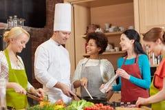 Les femmes et le chef heureux font cuire la cuisson dans la cuisine Image libre de droits