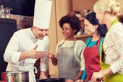 Les femmes et le chef heureux font cuire la cuisson dans la cuisine Photo stock