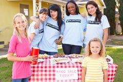 Les femmes et les enfants courant la charité font la vente cuire au four Photos libres de droits