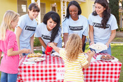 Les femmes et les enfants courant la charité font la vente cuire au four Photos stock