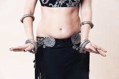 Les femmes exécute la danse de ventre dans la robe ethnique sur le fond beige images stock