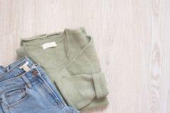 Les femmes façonnent des vêtements sur le fond en bois Regard dénommé par femelle plate de configuration Chandail et jeans Vue su photographie stock libre de droits