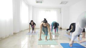 Les femmes faisant le yoga de guerrier posent après travail dans un studio lumineux de bien-être dans le mouvement lent - banque de vidéos