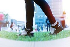 Les femmes font un pas en avant au succès, jeunes femmes fait un pas en avant sur l'herbe verte près du bâtiment d'affaires Photo stock