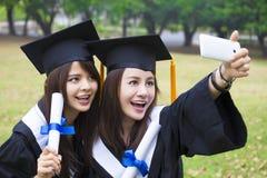 les femmes heureuses dans l'obtention du diplôme habille prendre la photo avec le pho de cellules Images libres de droits