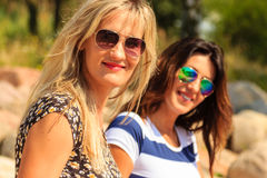 Les femmes heureuses exposent au soleil le bronzage et la détente sur la plage Photographie stock