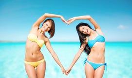 Les femmes heureuses faisant le coeur forment sur la plage d'été Image stock
