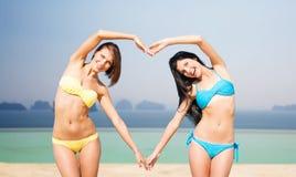 Les femmes heureuses faisant le coeur forment sur la plage d'été Images libres de droits