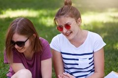 Les femmes heureuses parlant et riant en parc, se reposant sur l'herbe, portent les vêtements sport et les lunettes de soleil, en photos libres de droits