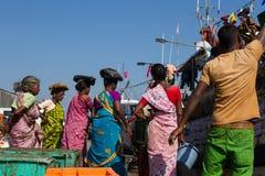 Les femmes indiennes dans des robes lumineuses attendent le déchargement du bateau de pêche Inde, Karnataka, 2017 Photos libres de droits