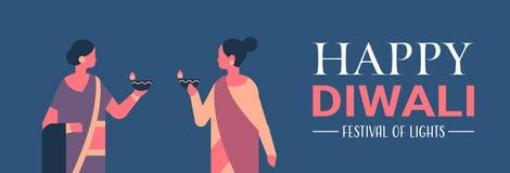 Les femmes indiennes de diwali heureux tenant la lampe à pétrole mirent la femme de concept de célébration portant les vêtements  illustration libre de droits