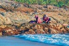 Les femmes indonésiennes assortissent le crochet de pêche en se reposant sur une roche par la mer le soir vague déferlante noire  photo libre de droits