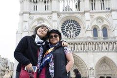 Les femmes mère d'Asain et le voyage de fille et la pose pour prennent la photo au Notre-Dame de Paris de Cathedrale Image libre de droits