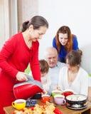 La femme en rouge verse le thé pour la famille Image stock