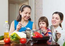 La femme mûre et sa fille avec le bébé font cuire le déjeuner Photos libres de droits