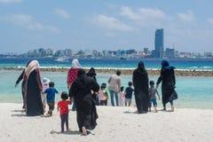 Les femmes maldiviennes et les enfants marchant vers l'océan à la plage tropicale image libre de droits