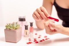 Les femmes manicure et des attachés une forme d'ongle pendant la procédure des prolongements d'ongle avec le gel à la maison Conc Photos libres de droits