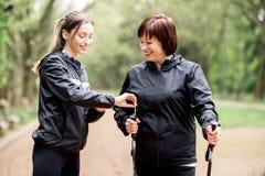 Les femmes marchant avec la hausse colle en parc Images stock