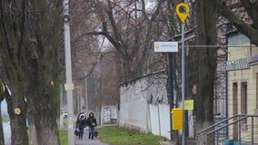 Les femmes marchent le long d'une rue de ville après le bureau de poste de la société UkrPoshta d'état Logo jaune sur une bo clips vidéos