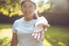 Les femmes mignonnes atteignent sa main pour l'aide donnent l'amour et la part Photo stock