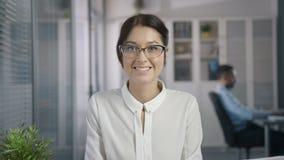 Les femmes mignonnes avec le beau regard dans l'endroit de gestion examine le cadre banque de vidéos