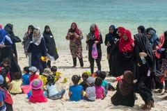 Les femmes musulmanes et les enfants ayant l'amusement à la plage photos libres de droits