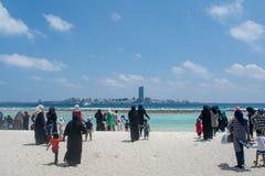 Les femmes musulmanes et les enfants marchant vers l'océan à la plage tropicale image libre de droits