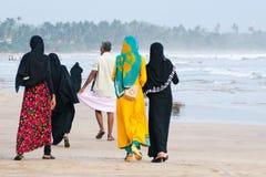 Les femmes musulmanes marchent le long de la plage, un homme marche en avant photographie stock libre de droits
