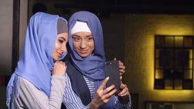 Les femmes musulmanes modernes prennent des photos à un téléphone portable Filles dans les hijabs parlant et souriant Image stock