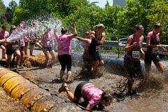 Les femmes obtiennent pulvérisés avec le tuyau d'incendie dans la piqûre de boue Image libre de droits