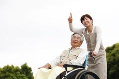 Les femmes ont aidé le fauteuil roulant Photographie stock