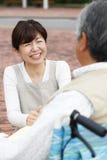 Les femmes ont aidé le fauteuil roulant Photographie stock libre de droits