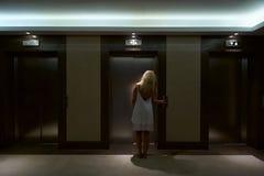 Les femmes ont appuyé sur le bouton de l'ascenseur Photographie stock libre de droits