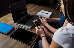Les femmes partner le message textuel de lecture sur le site Web par l'intermédiaire des téléphones de cellules Photos stock