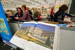 Les femmes regardent de nouveaux livres d'art la foire de livre d'intérieur Images stock
