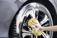 Les femmes remettent avec la roue de voiture de lavage d'éponge de mousse Images libres de droits