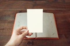 Les femmes remettent avec les photos vides sur l'album photos sur le fond en bois de table Album photos de livre ou de vintage av photo stock