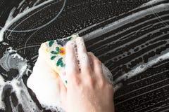 Les femmes remettent laver le fourneau électrique noir avec le détergent de savon Photos stock