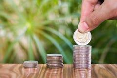 Les femmes remettent mettre des pièces de monnaie à la pile de pièces de monnaie photographie stock libre de droits