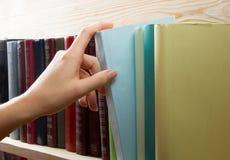 Les femmes remettent sélectionner le livre d'une étagère dans la bibliothèque De nouveau à l'école Images libres de droits
