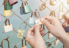 Les femmes remettent tenir la clé machine avec des serrures de rail de pont de l'amour Photos stock