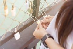Les femmes remettent tenir la clé machine avec des serrures de rail de pont de l'amour ainsi Photos libres de droits