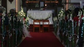 Les femmes s'asseyent sur la cérémonie de mariage dans l'église banque de vidéos