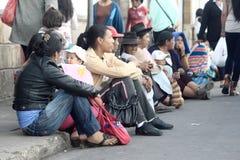 Les femmes s'asseyent sur le bordure, la rue dans le sucre Photographie stock